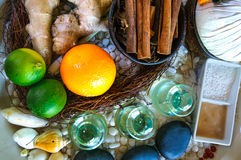 Top flat view of spa ingredients: oil in glass jars, orange, lyme, ginger, cinnamon sticks, stones, sand Stock Images