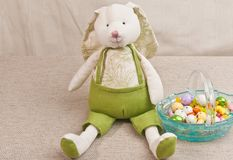 Stuffed, Easter bunny and  basket, filler with colorful, easter, candy. Top, front view, middle distance  of a stuffed, artisan, easter bunny and an artisan stock photo