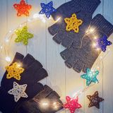 Woolen gloves without fingers mittens are opposite each other on a light wooden floor. On top of the garments are wicker stars and a luminous garland. Image for Stock Photography