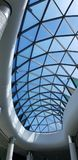 Top glass roof of a shopping mall. Top glass curved roof ceiling of a shopping mall with nice triangle pattern with blue sky on a background. modern Royalty Free Stock Photography