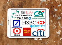 Top global banks icons and logos. Group of logos and brands of famous worldwide top banks on white tablet on rusted wooden background. banks like deutsche bank Stock Photos