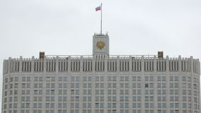 Top of government building in Russia with flag and crest. Against cloudy sky stock video footage