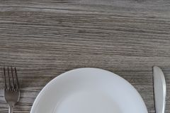 Top half of white empty plate, knife and fork on grey wooden tab stock photography