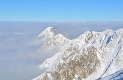 Top of high mountains, covered by snow and fog Stock Images
