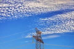 Top of high voltage pylon with nice sky with many clouds. Minimalist landscape with many small clouds, blue sky and top of high voltage pylon in nice afternoon Stock Image