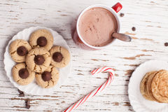 Top horizontal view of chocolate peanut blossom cookies. Top horizontal view of plate of snickerdoodle cookies, hot chocolate, peppermint candy cane, and Stock Photography