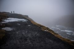 On the top of Icelandic waterfall in winter snow and rain, tourists walking. Dramatic  view inIceland from top down on a high waterfall, severe winter weather Royalty Free Stock Image