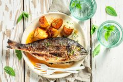 Grilled potatoes and seabream with tomatoes. Top view of grilled potatoes and seabream with tomatoes royalty free stock image