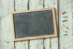 Top image of chalkboard and colorfull chalks over wooden table Royalty Free Stock Photo