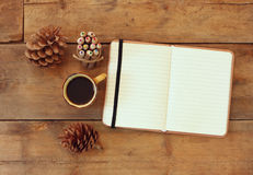 Top image of open notebook with blank pages, next to pine cones and cup of coffee over wooden table. retro filtered image Stock Photo