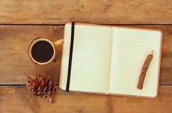Top image of open notebook with blank pages, next to pine cones and cup of coffee over wooden table. top image,. Top image of open notebook with blank pages royalty free stock photos