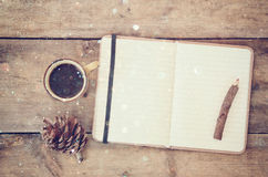 Top image of open notebook with blank pages, next to pine cones and cup of coffee over wooden table. top image, glitter overly.  stock images