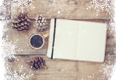 Top image of open notebook with blank pages, next to pine cones and cup of coffee over wooden table. top image, glitter overly wit