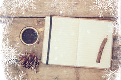 Top image of open notebook with blank pages, next to pine cones and cup of coffee over wooden table. top image, glitter overly wit Royalty Free Stock Photography