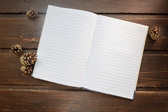 Top image of open notebook with blank pages, next to pine cones. Over wooden table. Flat lay style royalty free stock image