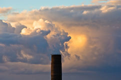 Top of industrial chimney against colorful and picturesque golden clouds Royalty Free Stock Images