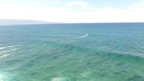 Top 4k aerial drone view of windsurfer gliding slowly in summer waves of turquoise blue ocean water in Hawaiian seascape stock footage