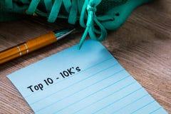 Top 10 - 10K concepto del paseo del funcionamiento del ` s en el cuaderno y el tablero de madera Imagen de archivo libre de regalías