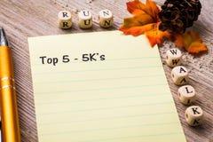 Top 5 - 5K concepto del paseo del funcionamiento del ` s en el cuaderno y el tablero de madera Imagen de archivo libre de regalías