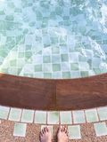 Top of lady feet standing over swimming pool, stair of swimming pool Stock Photography