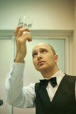 A top-level waitstaff checking the cleanness. Young handsome bald waiter dressed in a white shirt and a vest and a bow-tie is polishing a glass and staring at it Royalty Free Stock Photos