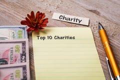 Top 10 Liefdadigheidsconcept op notitieboekje en houten raad Royalty-vrije Stock Afbeeldingen