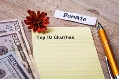 Top 10 Liefdadigheidsconcept op notitieboekje en houten raad Royalty-vrije Stock Foto's