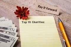 Top 10 Liefdadigheidsconcept op notitieboekje en houten raad Royalty-vrije Stock Afbeelding