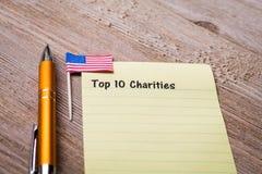 Top 10 Liefdadigheidsconcept op notitieboekje en houten raad Stock Foto