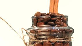 Top of little spinning bottle with coffee beans. Beautiful, little spinning bottle with roasted coffee beans and cinnamon, close up, on white background stock footage