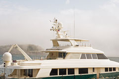 Top of luxury yacht. A closeup view of the top decks and superstructure of a luxury yacht in a marina on a foggy day Stock Photography