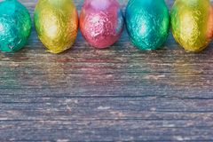 Row of colored chocolate eggs against wooden background with copy space stock photo