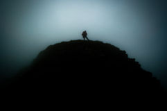 On top. A man / hiker sitting on top of a mountain. Only silhouettes are visible, the large black portions leaving a lot of space for text Stock Photography