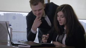 Top manager and businesswoman talking in office using portable computer. Top manager and businesswoman in business suits talk positively in creative office, use stock footage
