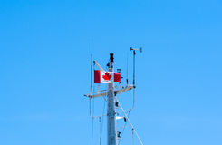 Top of metal ship mast with Canadian flag on blue sky Royalty Free Stock Photo