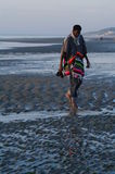 Top model in poncho walking on sandy strange beach. Front of a man walking on a norman beach at low tide Stock Image