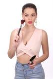 Top modelo del rosa que lleva que presenta con el cepillo del maquillaje Cierre para arriba Fondo blanco Foto de archivo libre de regalías