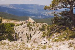 At the top of mount AI-Petri, the cable car building, pine and a scattering of stones in the foreground.  royalty free stock photo