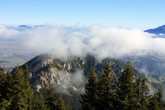 On top of the mountain and above the clouds Stock Photos