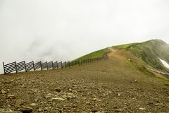 Top of the mountain and road in mountains with a fence. is cloudy also fog. Top of the mountain and road in mountains with a fence Royalty Free Stock Photography