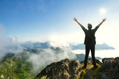 Top of a mountain. Teenager boy with backpack standing on top of a mountain with raised hands Stock Images