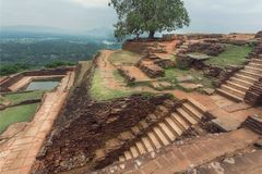 Top mountain view from Sigiriya rock to rural road in Sri Lanka. UNESCO world heritage site. Top mountain city Sigiriya with rural landscape, water pool and Royalty Free Stock Photo