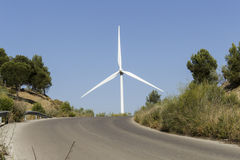 Top of a mountainous road. With pines and a big windmill in the blue sky background Royalty Free Stock Photography