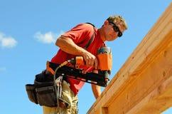 Top nail building contractor worker air gun nailer working corner