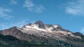 Top nevado de la montaña debajo de un cielo azul con las nubes wispy fotos de archivo