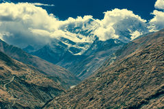 Top nevado de la montaña engullido en nubes imagen de archivo
