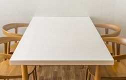 Top and Oblique of white table. In white room and wooden floor. Four wooden chait. Empty space on white table Royalty Free Stock Images
