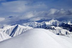 Top of off-piste snowy slope and cloudy mountains Royalty Free Stock Photography