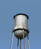 Top of an old fashioned water tower isolated. Close-up of the top of a rusty gray metal old fashioned water tower with graffiti. Isolated against a blue sky with stock images