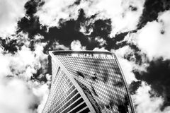 The top of one building of business complex Moscow City in cloud. S. A lot of glass and concrete in modern architecture. Toned Stock Photo